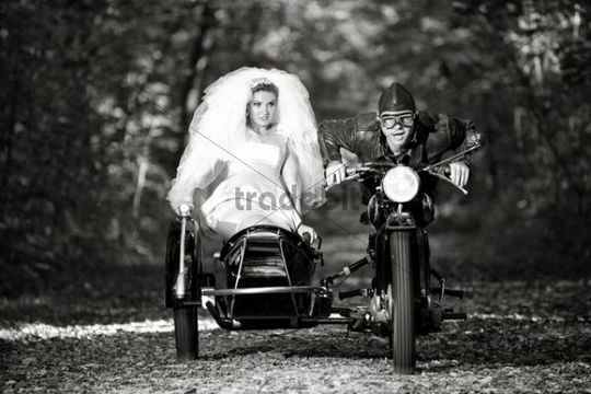 Bride and groom driving to their wedding in a motorcycle with sidecar