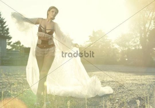 Young woman wearing lingerie in the evening sun