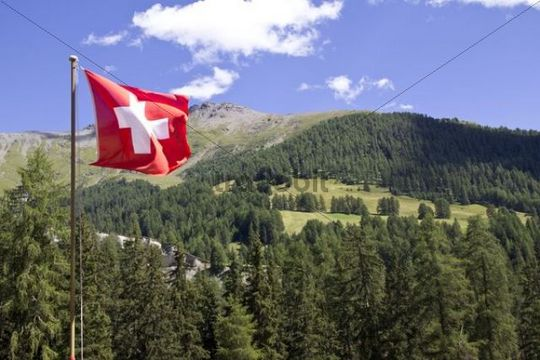 Mountain landscape with a Swiss national flag, Lower Engadine, Graubuenden or Grisons, Switzerland, Europe