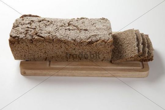 Loaf of whole grain bread and bread slices on a wooden board