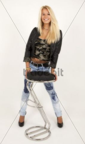 Young woman with long blond hair wearing a jacket, light blue jeans and high heels posing, standing behind a bar stool