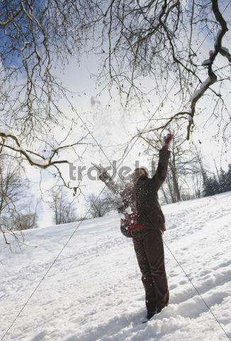 Woman throwing snow into the air, Landshut, Lower Bavaria, Bavaria, Germany, Europe