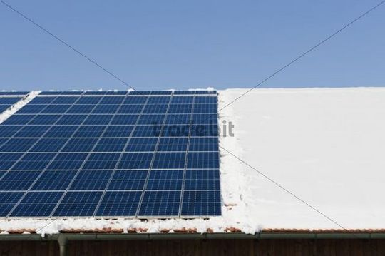 Solar cells cleared of snow on a roof in winter, Landshut, Lower Bavaria, Bavaria, Germany, Europe