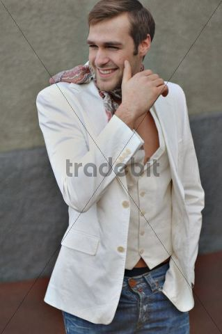 Man in white jacket and jeans in front of a wall