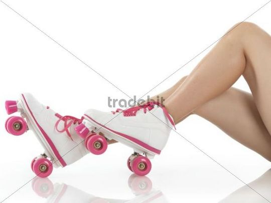 Closeup of legs of a young woman wearing white with pink classic roller girl derby skates