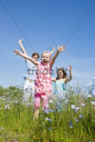 A mother and her two daughters running joyfully across a flower meadow