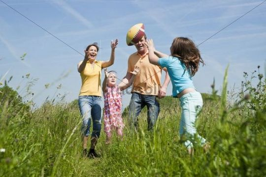 Family playing joyfully with a ball in a flower meadow