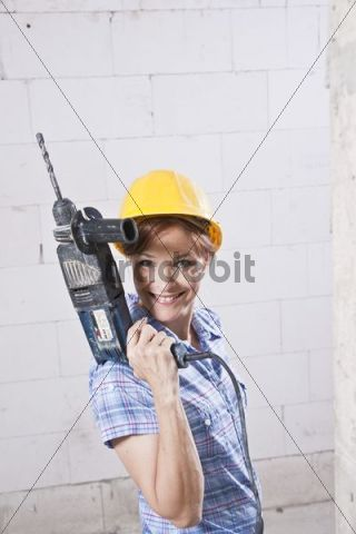Craftswoman with hard hat and drill machine