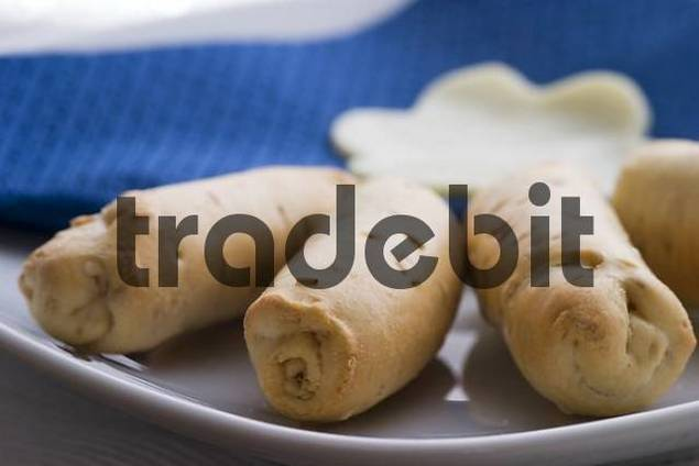 Bunch of crunchy breadsticks with cheese in a dish - close up