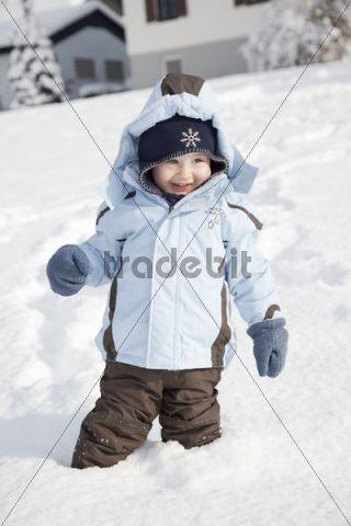 Little boy standing in deep snow