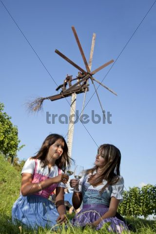 Two young Styrian women sitting in front of a Klapotetz, a wind-rattle scarecrow, on a meadow holding wine glasses, Southern Styria, Styria, Austria, Europe