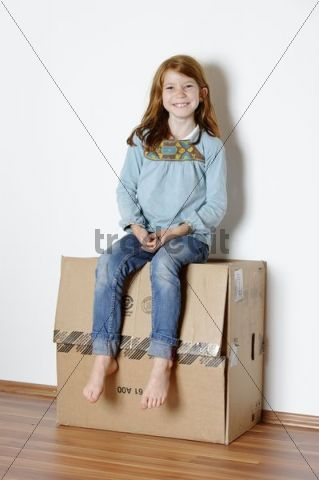Girl sitting on a cardboard box, packing case