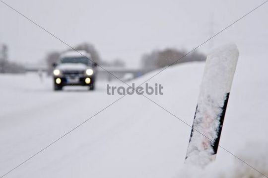 Country road covered with snow, with a sidepost and a car, near Bondorf, Baden-Wuerttemberg, Germany, Europe