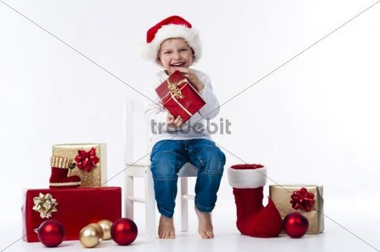 Boy with Santa hat and Christmas gifts