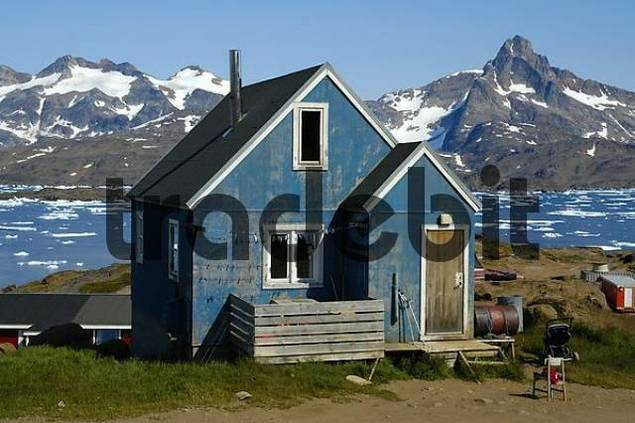 Old blue painted house in front of fjord with ice pack and snow-capped mountains Ammassalik Eastgreenland