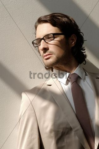 Fashion shoot, a man wearing glasses and a suit in the sunlight