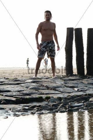Muscular man wearing swimming trunks standing on a beach