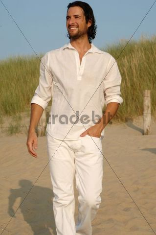 Man wearing white clothes walking in the dunes on the beach