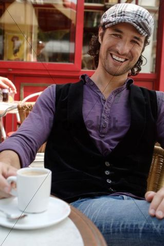 Man, early 30s, wearing casual clothes sitting in an outdoor café with a coffee cup, smiling