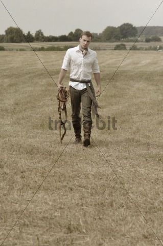 Man wearing riding clothes walking in a field in summer