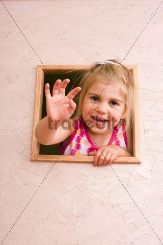 Girl, 3 years, waving through window