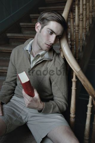 Man with book in a stairwell, nostalgic portrait
