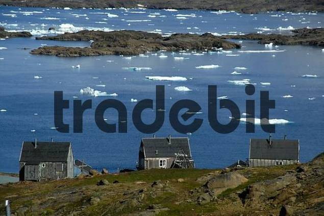 Old grey wooden houses above a fjord with ice-pack Ammassalik Eastgreenland