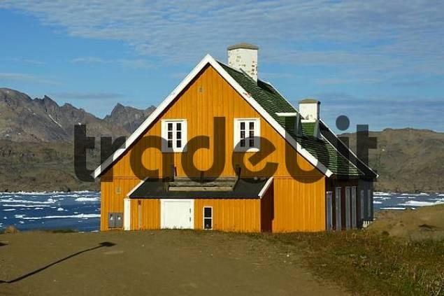 Ochre coloured house at a fjord in settlement Ammassalik Eastgreenland