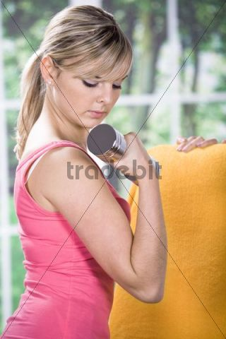 Young woman doing exercises with dumbbell