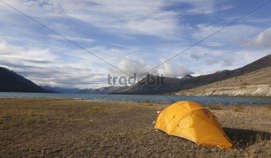 Tent on the shore of Kusawa Lake, mountains behind, Yukon Territory, Canada