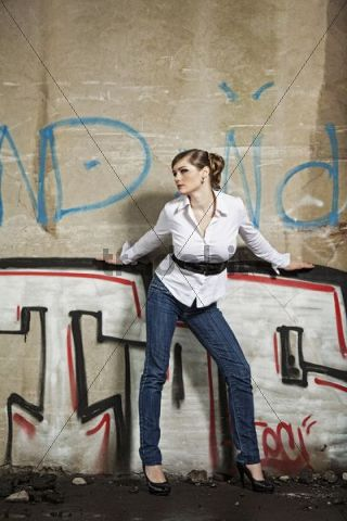 Young woman wearing jeans and high heels posing in front of a wall covered in graffiti