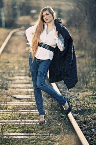 Young woman posing with jacket, standing on a railway track