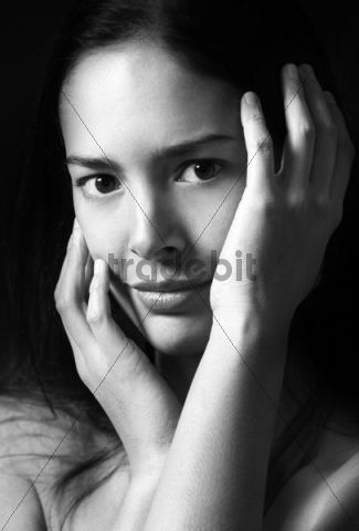 Young woman, hands framing face, portrait