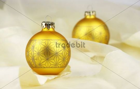 Two gold baubles on a chiffon cloth