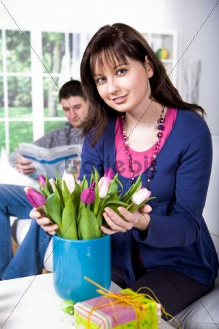 Young woman arranging tulips in a vase