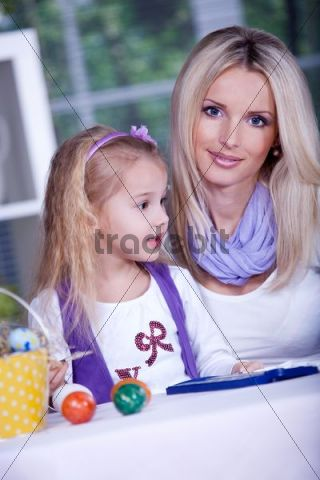 Little girl painting Easter eggs with her mother