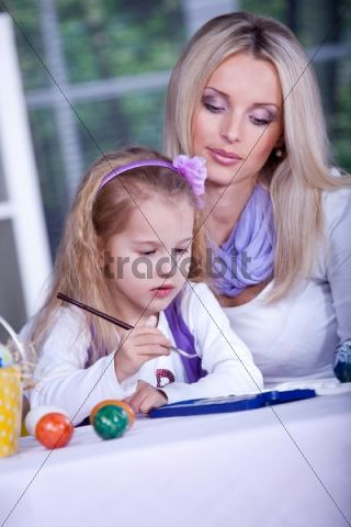 Little girl painting Easter eggs while mother is watching