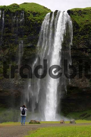 female tourist taking photos at the Seljalandsfoss-waterfall in Iceland