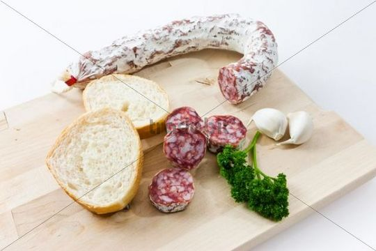 Gourmet salami, premium salami with French bread, garlic and parsley on a wooden board