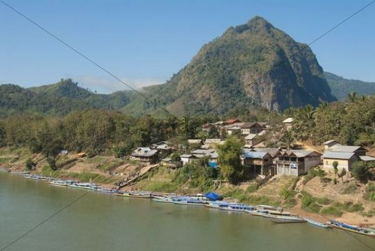 Village in front of a mountain, many boats on the shore, Nam Ou river, Muang Ngoi Kao, Luang Prabang province, Laos, Southeast Asia, Asia