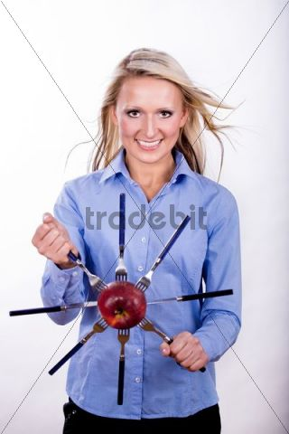 A young woman holding an apple with forks as steering wheel