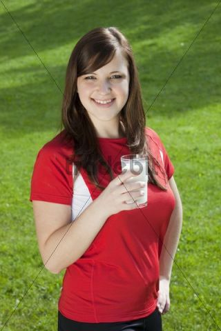 Young smiling woman wearing sports clothing and holding a glass of milk in her hand