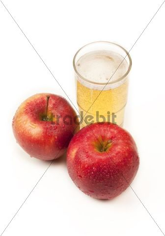 Two apples beside a glass of apple juice