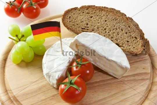 German Camembert chees on a board with grapes, bread and tomatoes