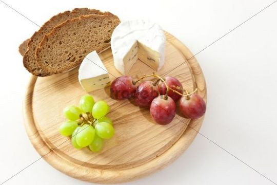 Blue cheese on a board with bread and grapes