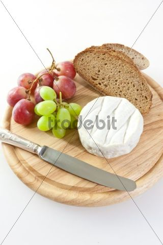 Chardonnay cheese on a board with grapes and bread