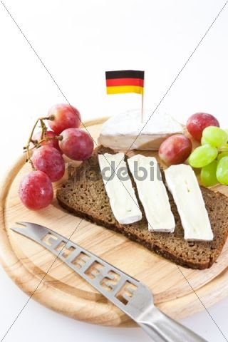 German Camembert cheese on a board with grapes, bread and tomatoes