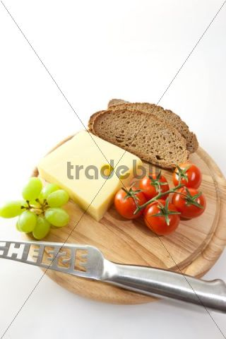 Emmental cheese on a board with grapes, bread and tomatoes