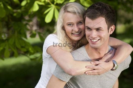 Young woman embracing a young man in a park in spring