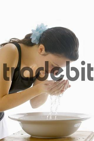Young woman takes water out of a washbowl